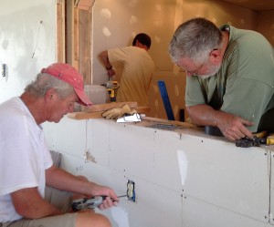 Gary takes a break from installin 4(four) AC units to give Don some support with Terry doing sheetrock in backgroud.